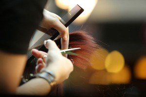 Shear Artistry hair stylist cutting clients hair with comb and scissors